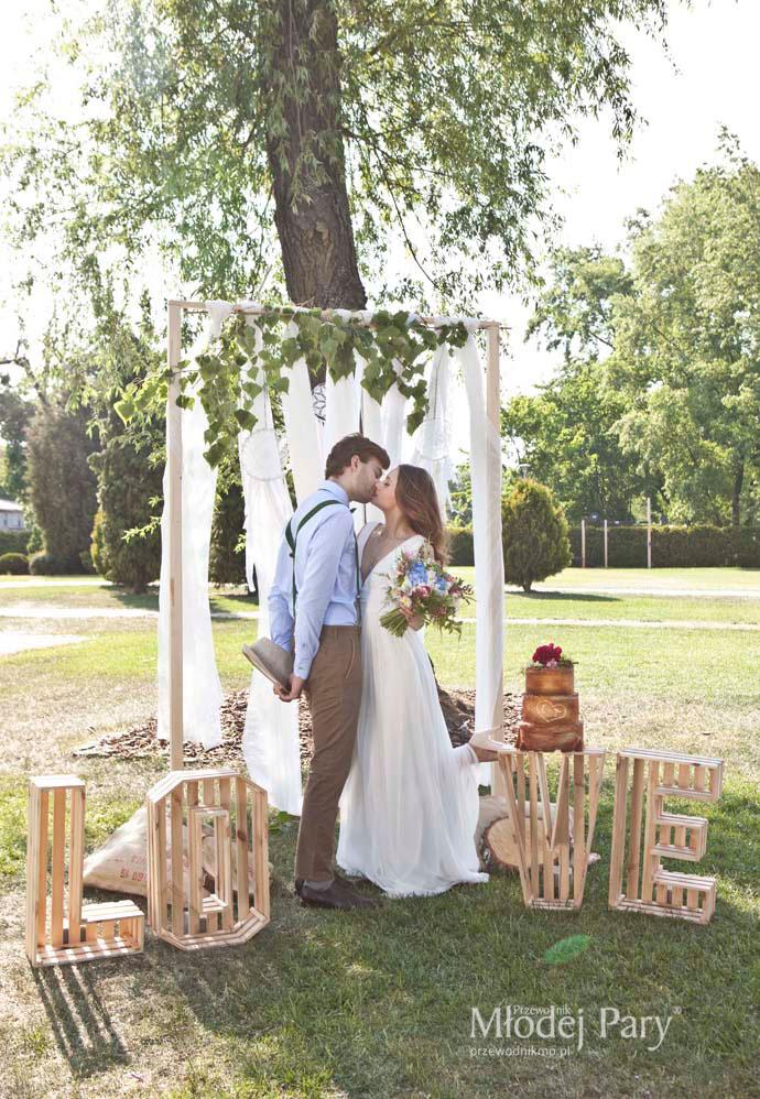 Młoda para pod rustykalnym łukiem ślubnym
