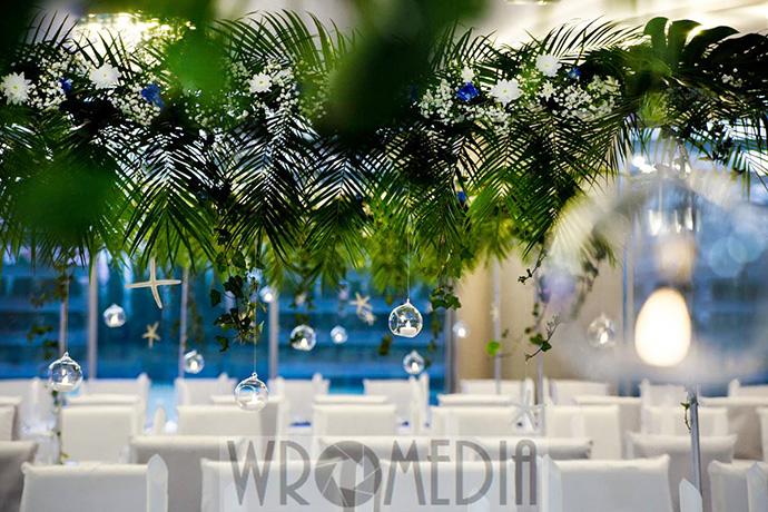Stoły weselne przyozdobione egzotycznymi liśćmi