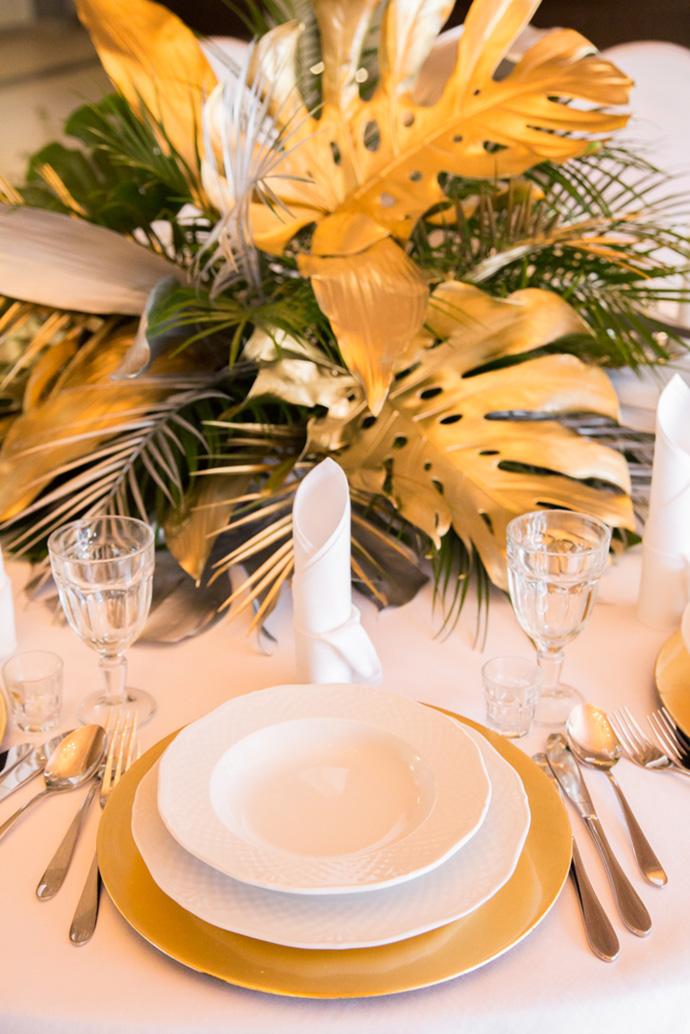 Złote podtalerza na weselu i dekoracja ze złotą monsterą