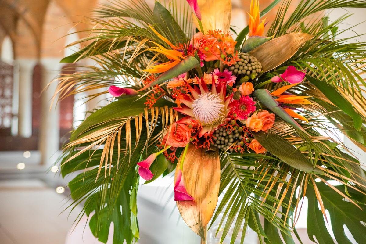 Coral wedding z protea i monsterą stół weselny
