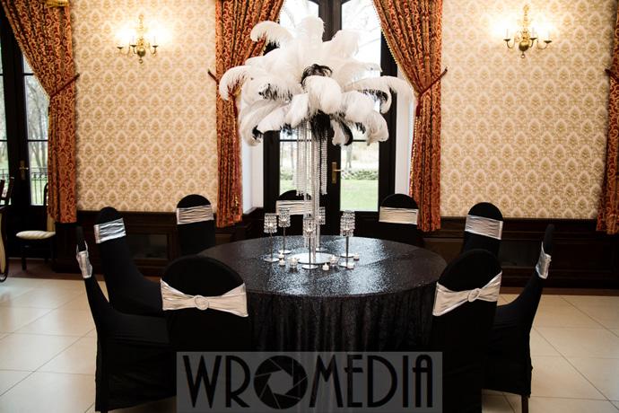 Czarny ozdobny obrus na wesele i czarno-białe pióra