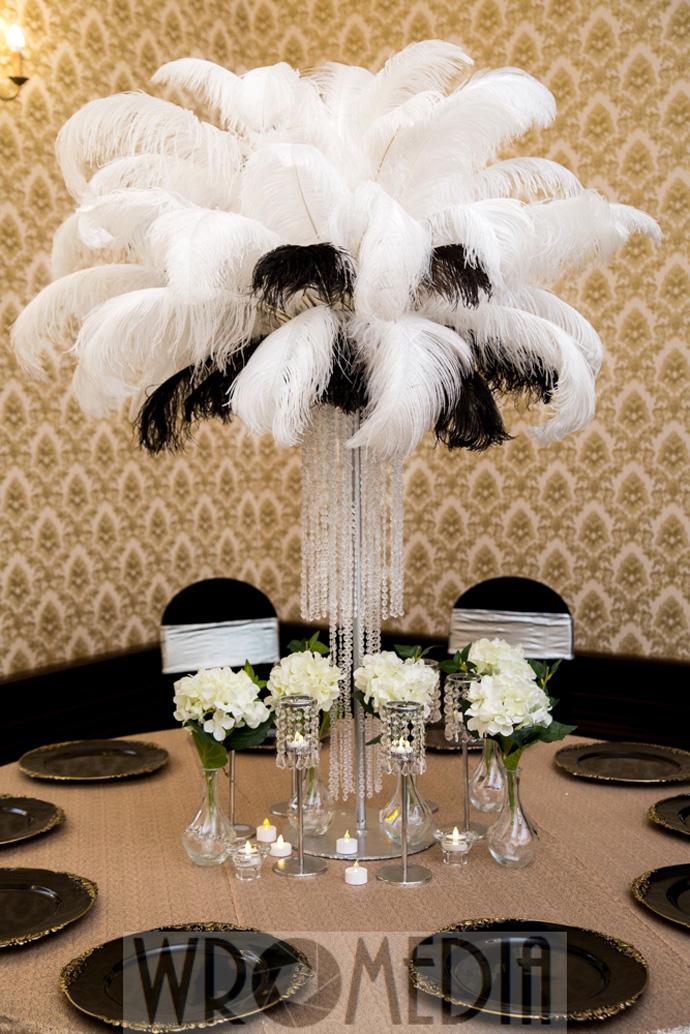 Czrno-biała dekoracja ślubna z metalicznym obrusem, piórami i kwiatami