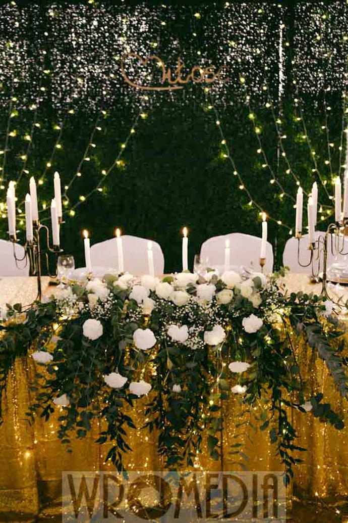 Stół młodej pary z zieloną ścianką i biało-zielonymi kwiatami