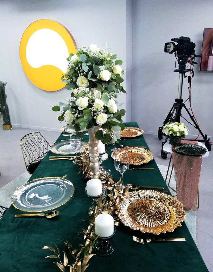 Zielony obrus, złote podtalerze, kwiatowa dekoracja z białymi kwiatami