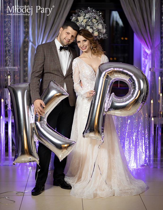 Młoda para trzyma srebrne balony inicjały