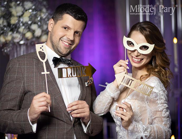Młoda para z zabawnymi akcesoriami weselnymi