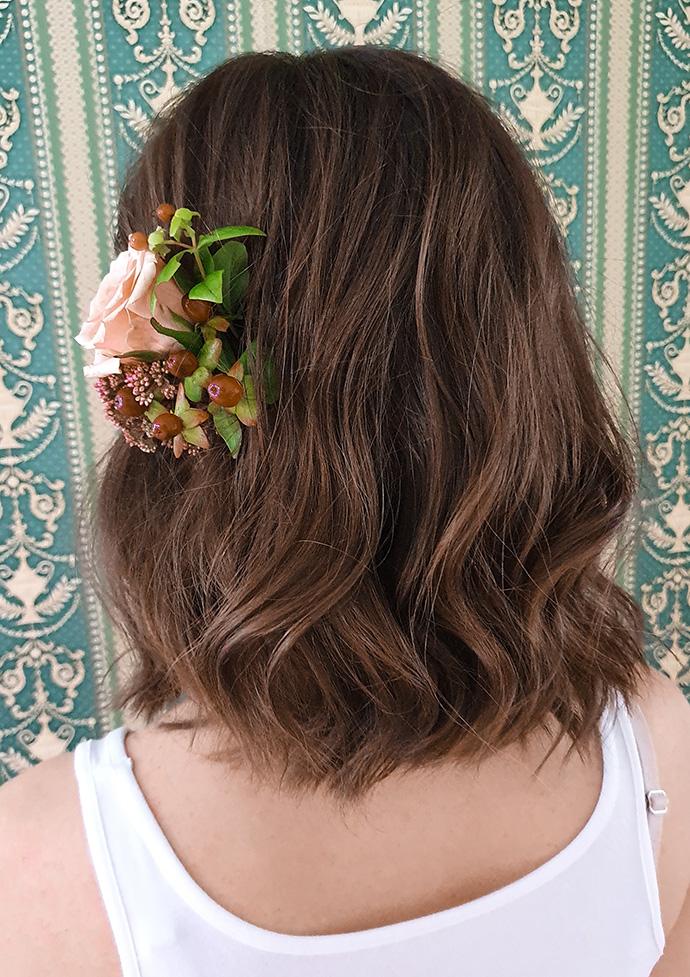 Średniej długości włosy lekko pofalowane z ozdobą z kwiatów