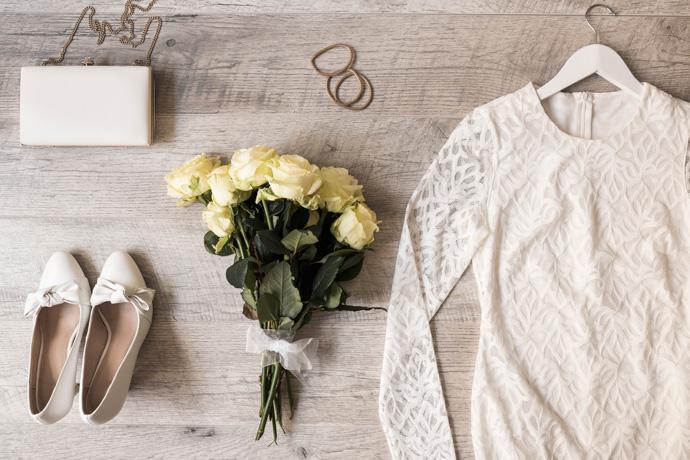 Bukiet z żółtych róż, biała suknia ślubna, buty, torebka